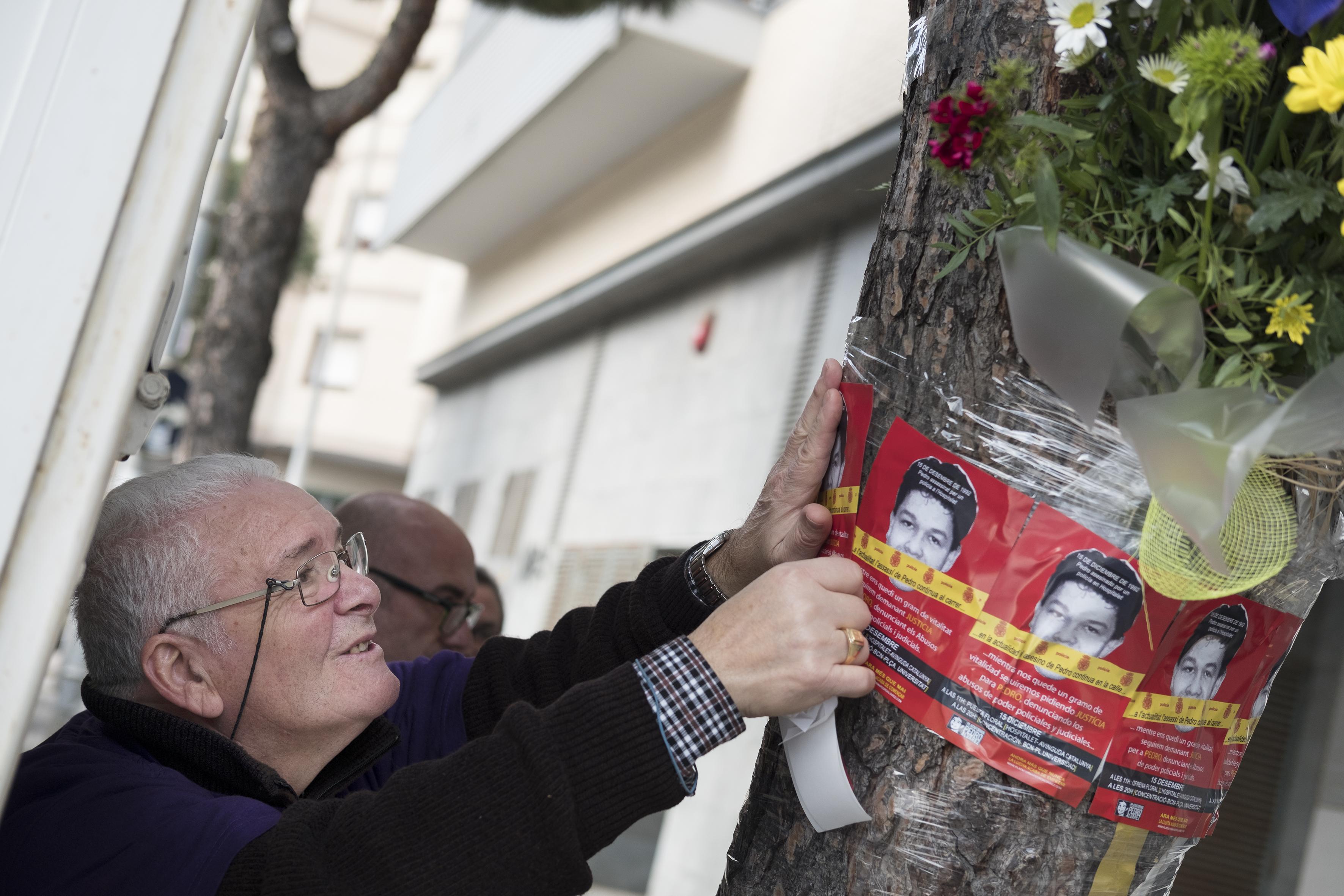 Juanjo Alvarez, en homenaje a su hijo Pedro Alvarez, joven asesinado por un policia nacional un 15 de diciembre de 1992, pega adhesivos alrededor de la ofrenda floral. Hospitalet del Llobregat, 2016 ©Patricia Bobillo Rodriguez