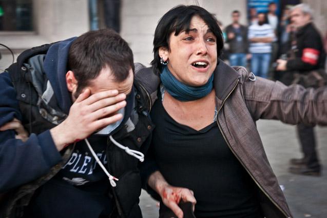 La compañera de Angelo Cilia lo acompaña hacia la ambulancia, después de recibir un impacto de bala de goma que le reventó un ojo | Foto: JORDI BORRÀS